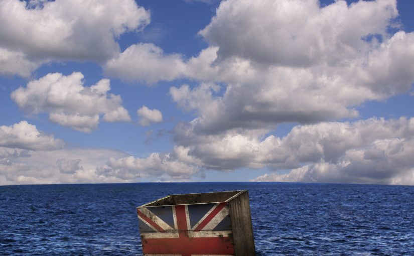 A metaphorical image of a single worn wooden crate, floating alone in the ocean, with a stencilled British flag on the front.